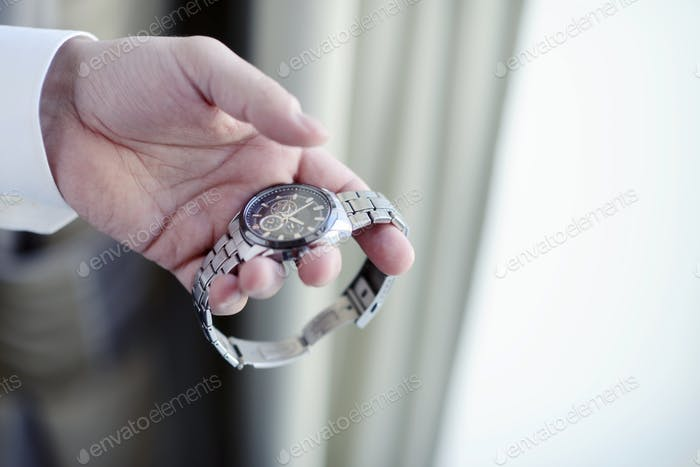 Groom is wearing a wrist watch indoors
