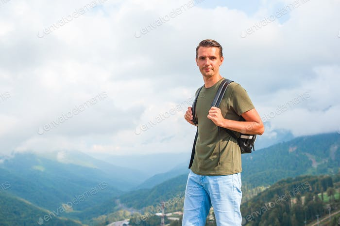 Tourist man in mountains in the background of fog
