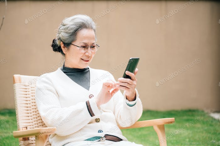 Senior woman video chatting with smartphone outdoors