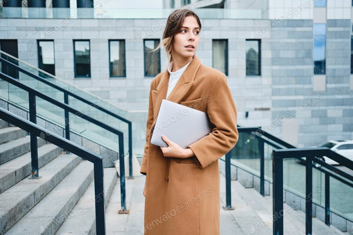 Young pensive businesswoman in coat with laptop dreamily looking away outdoor