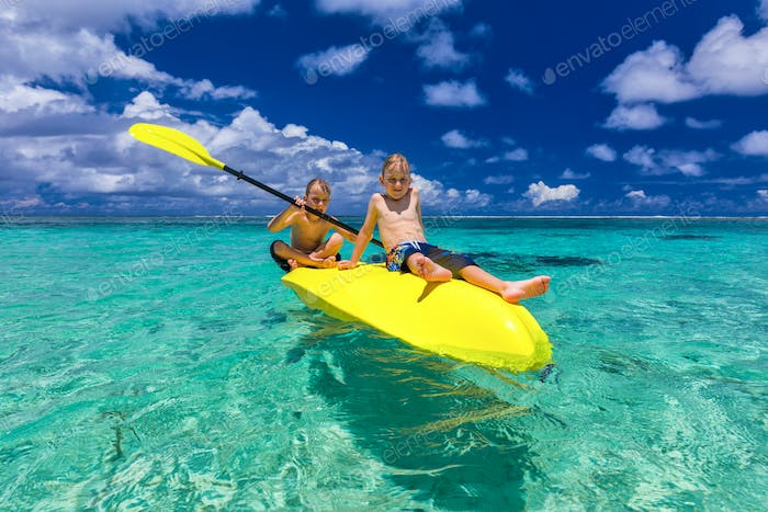 Two young caucasian boys kayaking at tropical sea on yellow kaya
