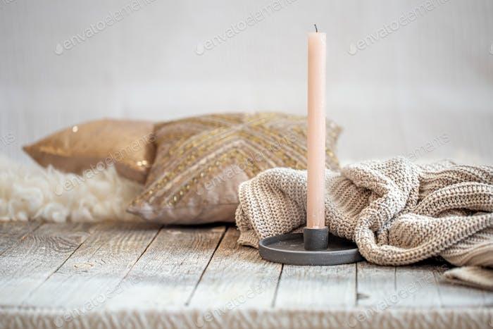 Hintergrund mit einem kuscheligen Strickpullover und einer Kerze.