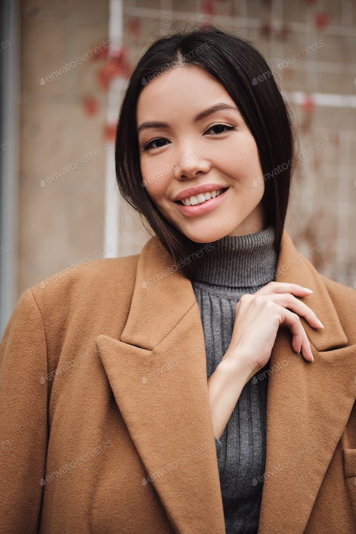 Portrait of gorgeous Asian girl in coat happily looking in camera outdoor
