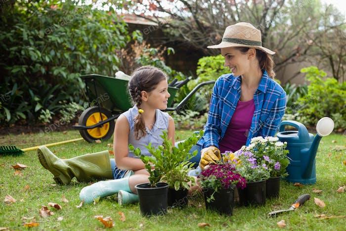 Lächelnde Mutter und Tochter sitzen mit verschiedenen Topfpflanzen