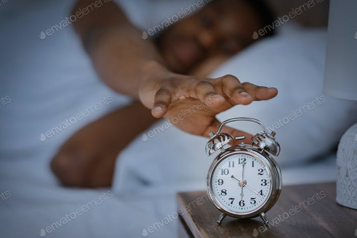 Sleepy African Man Turning Off Alarm-Clock Waking Up At Home