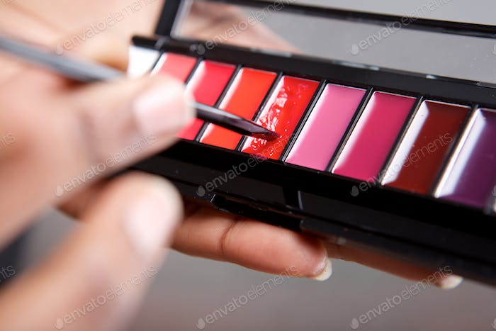 Close up woman holding lip gloss color palette and makeup brush