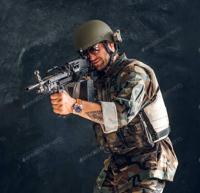 Military guard is holding his machine gun
