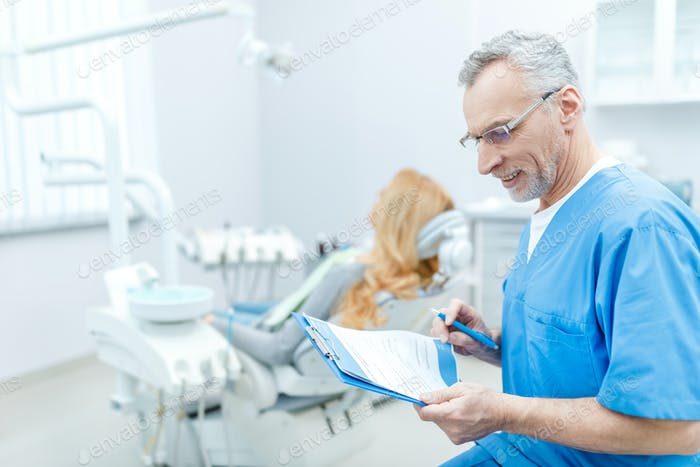 senior dentist in uniform with clipboard in dental clinic with patient behind