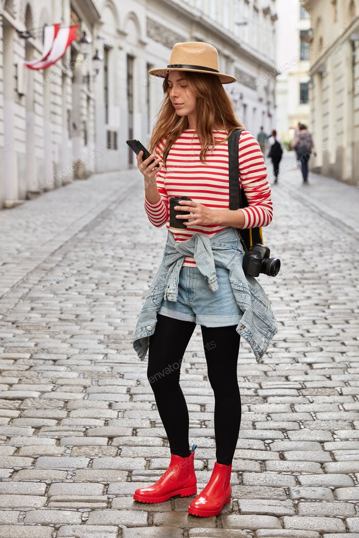 Vertical shot of fashionable woman wears hat, striped jumper, jeans short and rubber red boots, hold
