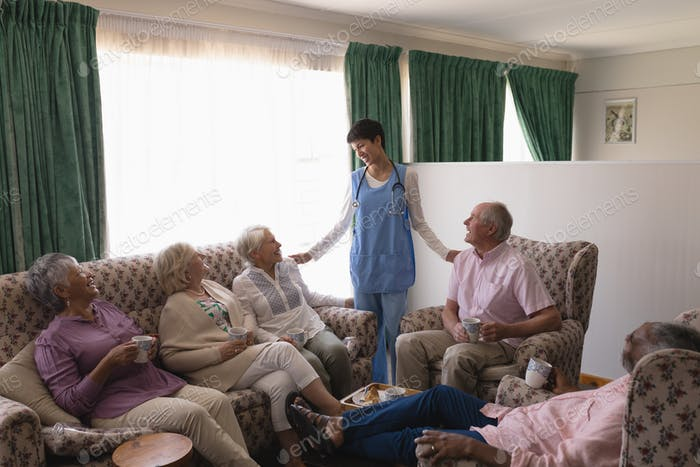 Female doctor interacting with senior people in living room at home