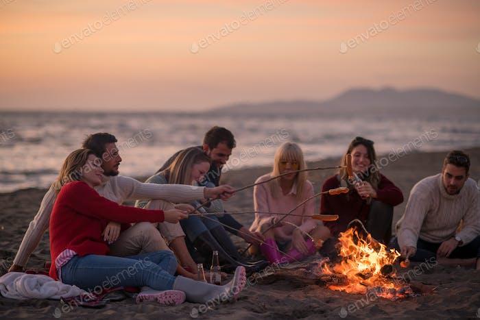 Grupo de jóvenes Amigos sentado por el fuego en Playa
