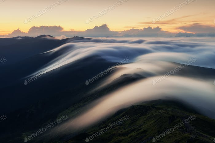 Amazing flowing morning fog in spring mountains