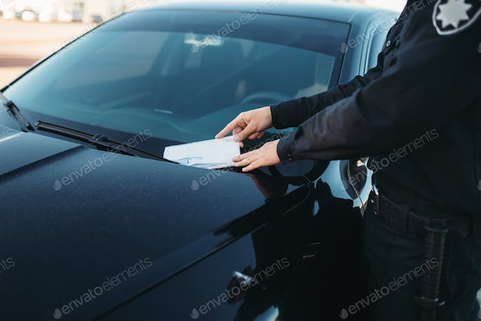 Male policeman in uniform writes a fine on road