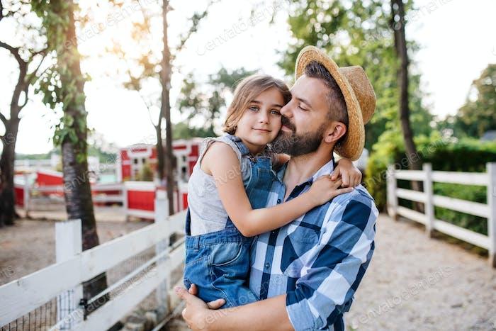 Ein Vater mit kleiner Tochter zu Fuß im Freien auf Familienfarm
