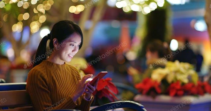 El uso de la mujer del teléfono móvil sobre el fondo de desenfoque de luz dorada