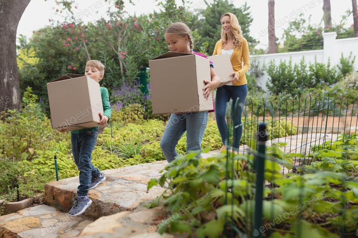 Front view of Caucasian mother and children with cardboard boxes walking towards home