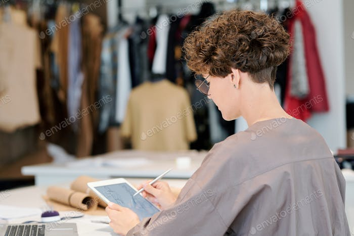 Young creative fashion designer with tablet making digital sketches