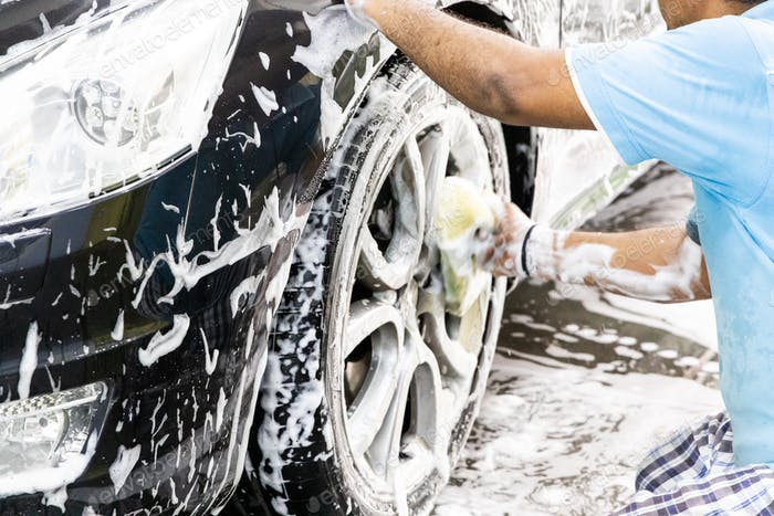 Worker wipe clean car using detergent soap foam with cloth