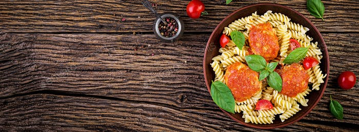 Fusilli  pasta with meatballs in tomato sauce and basil in bowl. Italian cuisine. Top view. Banner