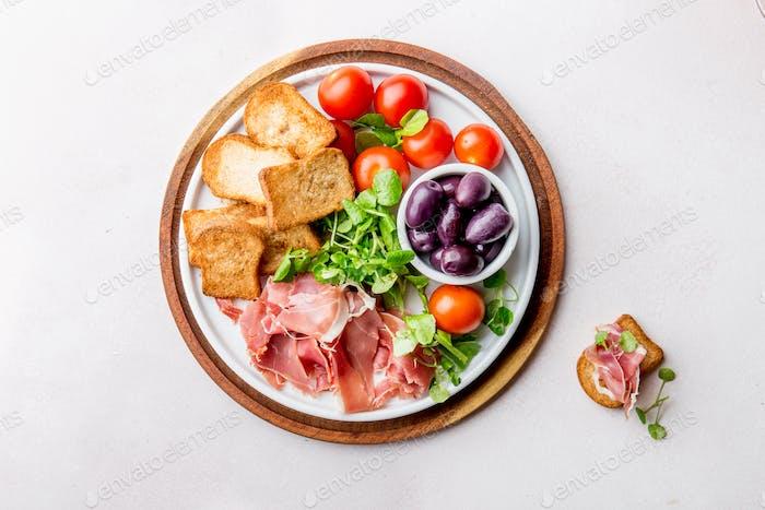 Antipasto Teller mit getrocknetem Brot, Schinken Serrano, Tomatenkirsche und lila Oliven. Weißer Hintergrund.