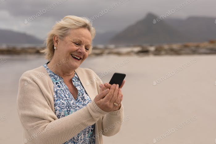 Happy senior woman using mobile phone standing at the beach with mountains in the background
