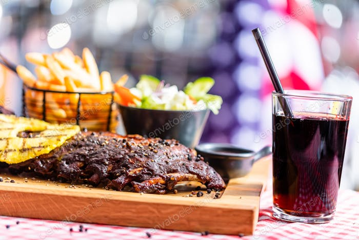 Ribs with salad, french fries and cola served in american restaurant