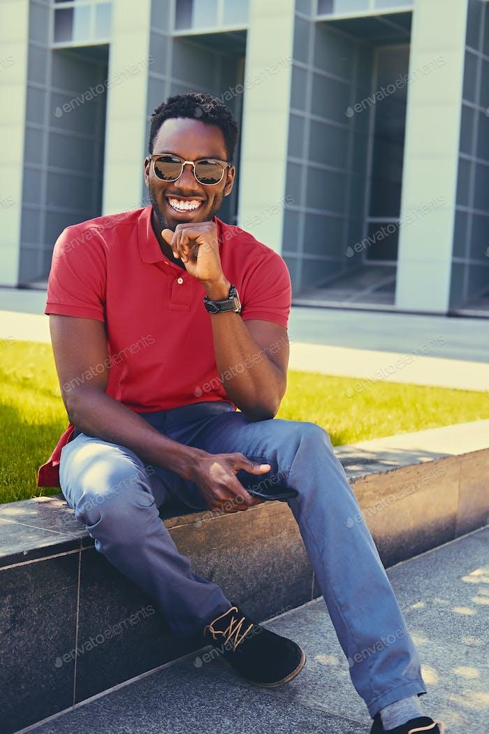 Черный человек над современным строительным фоном.