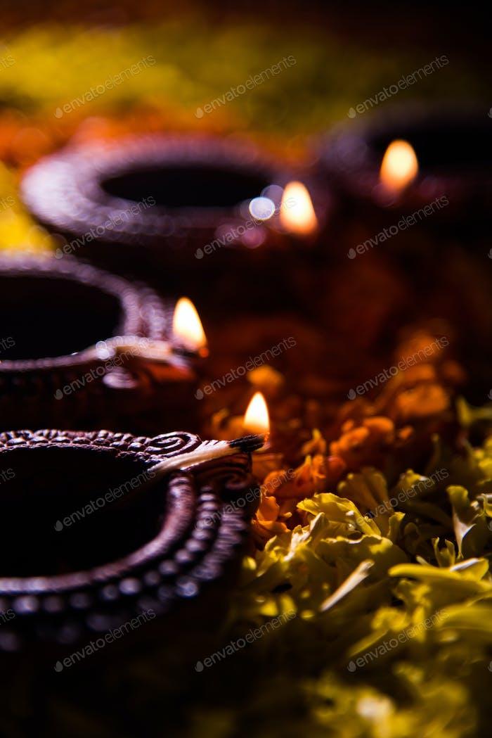 Happy Diwali - Diya Over Flower Rangoli