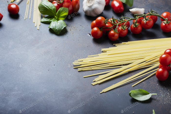 spaghetti, tomato, basil and garlic on the black table