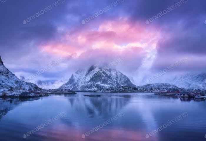 Aerial view of snowy mountain, village on sea coast, purple sky