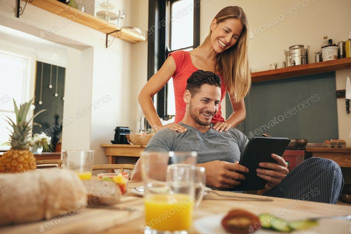 Beautiful couple in kitchen and using a touchpad
