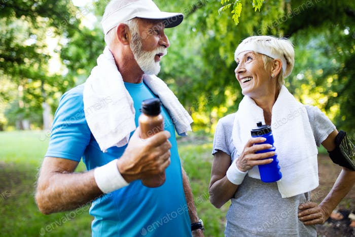 Beautiful senior couple running outside in forest