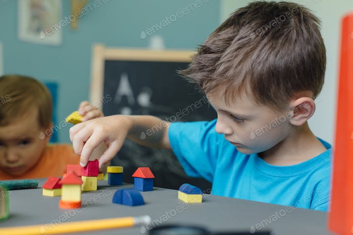 Two brothers playing with wooden blocks