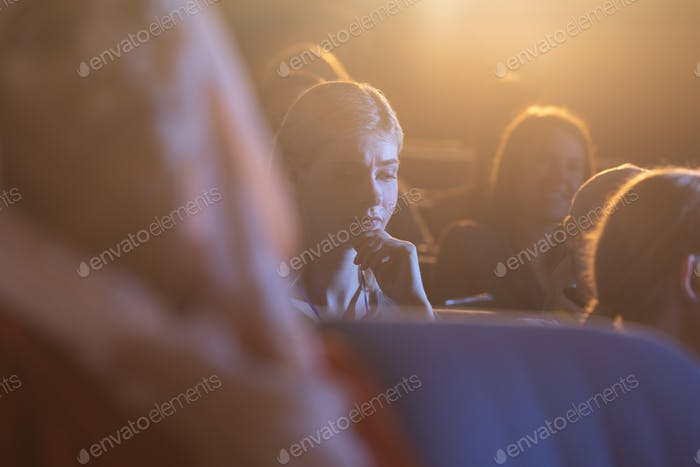 Young businesswoman thinking and looking down while sitting in the auditorium