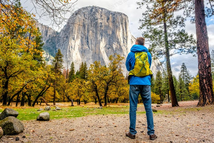 Tourist with backpack hiking in Yosemite National Park Valley at cloudy autumn morning