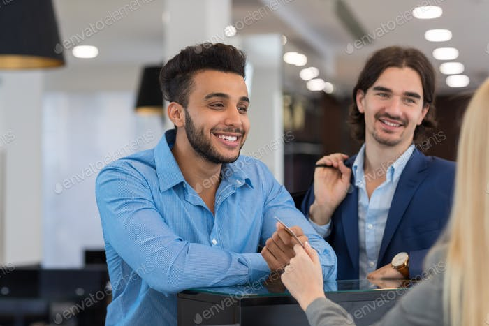 Happy Smiling Business Man Give Credit Card To Female Shop Assistant Paying For Clothes