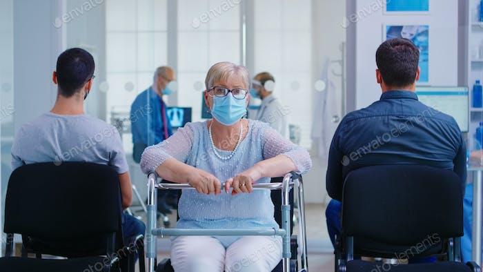 Mujer mayor con andador en el área de espera del hospital