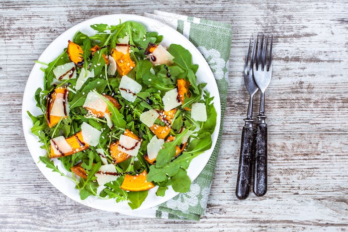 Salad with baked pumpkin, arugula, parmesan and sesame