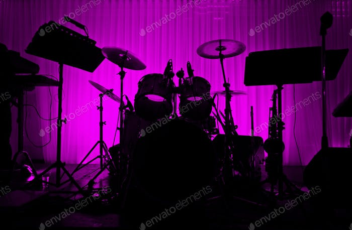 Drum in silhouette with no musician.