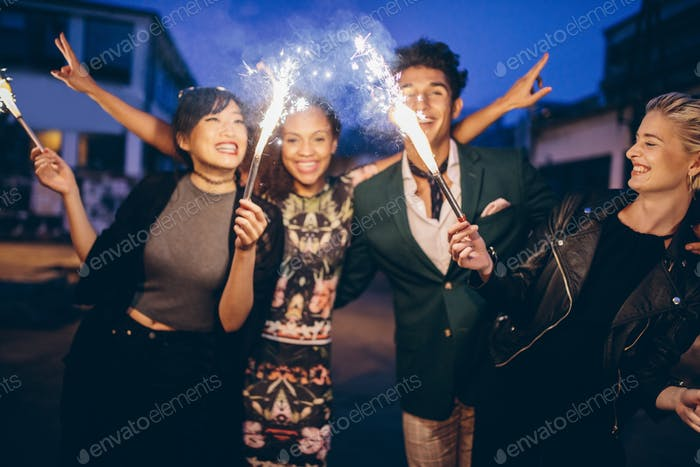 Young friends having night party with sparklers