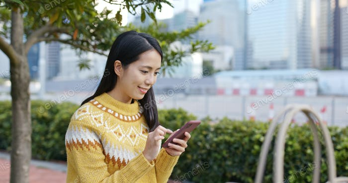 Woman check on mobile phone and sit at outdoor