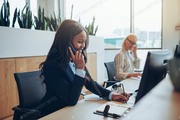 Young African American businesswoman smiling and talking on a telephone