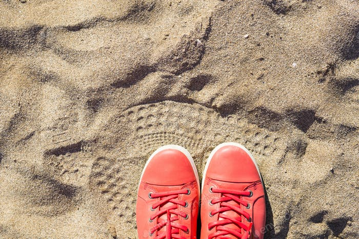 Concept with pink sneakers on bright sea sand. Summer vacation background with space for the text