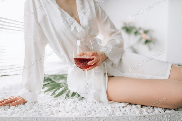 Female person with glass of wine sitting in bath