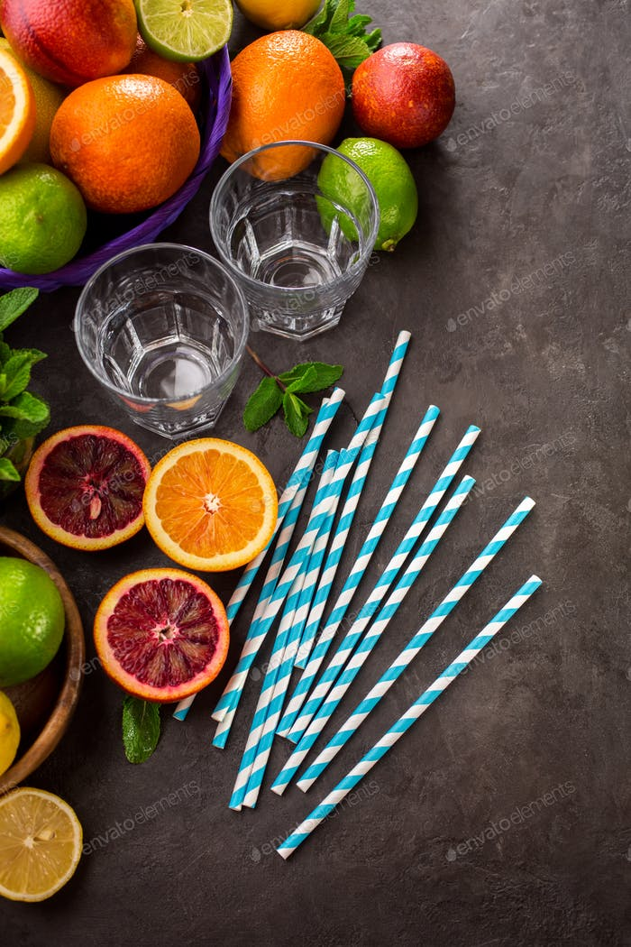 Citrus fruits, glass, straws and mint over dark background