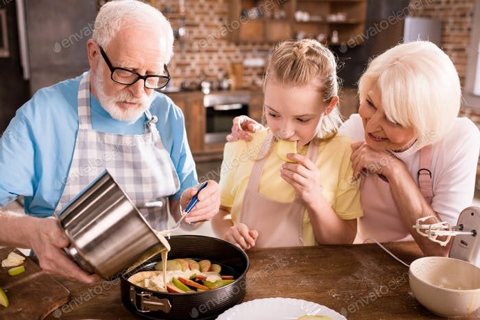 grandparents and girl cooking together at home