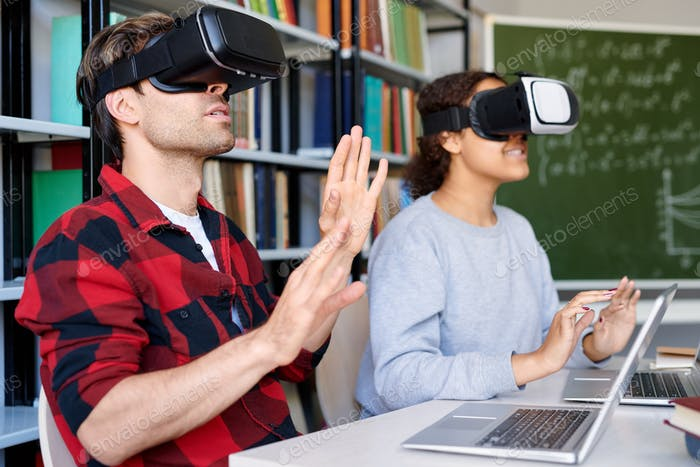 Young man and his classmate in vr goggles touching virtual display
