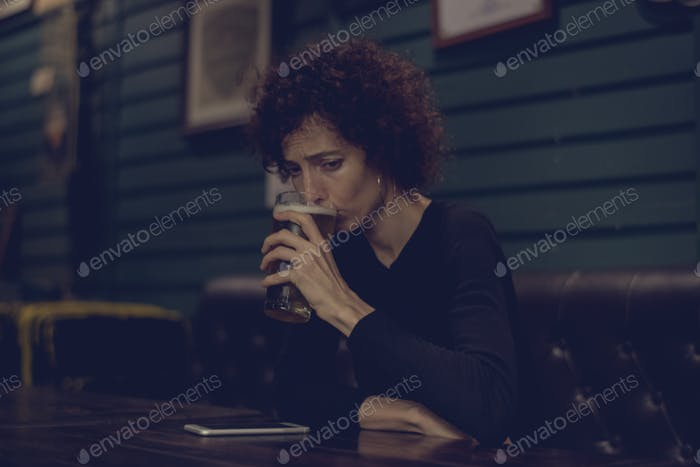 Woman having a beer at a bar