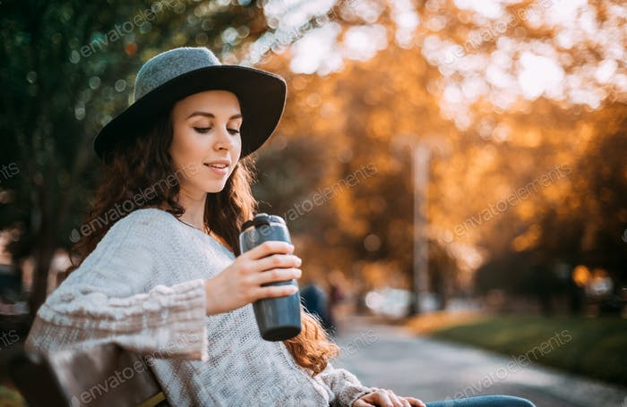 Stylish young woman walking in autumn city with thermo mug