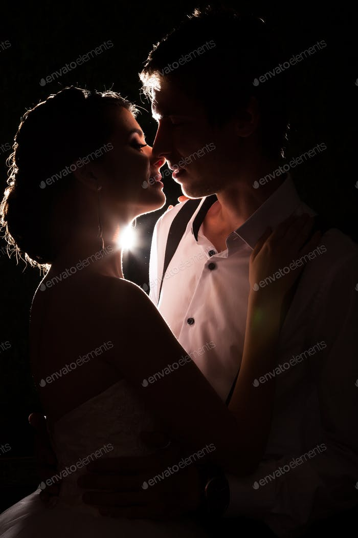 Beautiful bride and groom together backlit